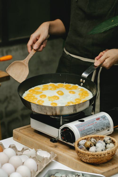 Crop faceless cook frying quail eggs on pan