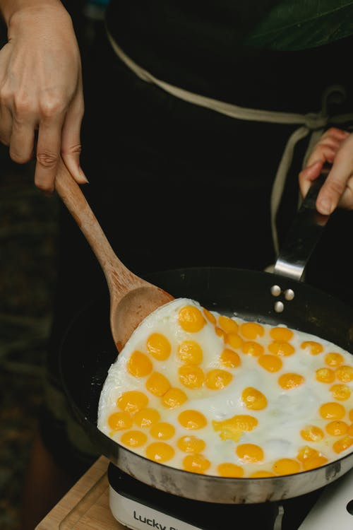 Crop faceless chef frying quail eggs