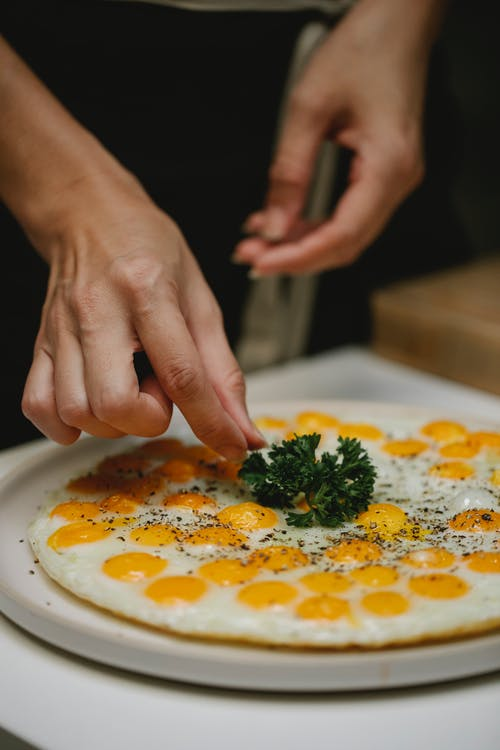 Crop anonymous housewife serving delicious freshly fried quail eggs and garnishing with herb in kitchen