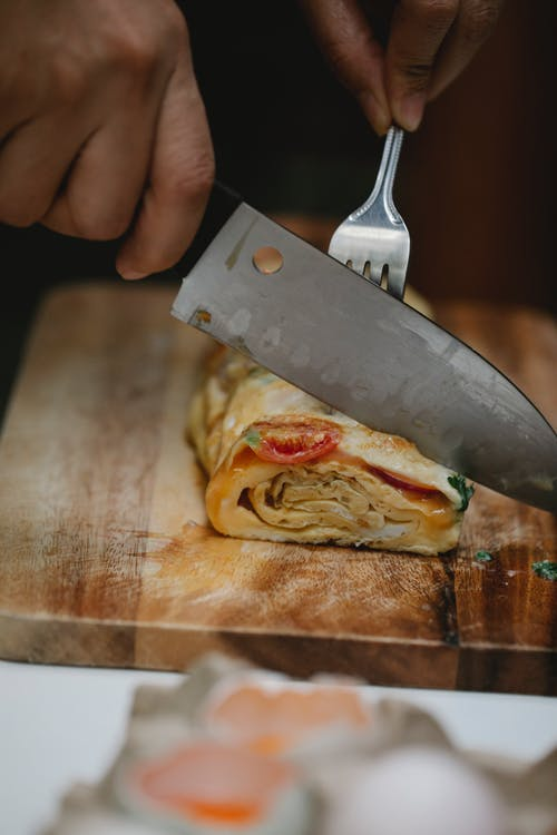 Crop anonymous chef with sharp knife and fork cutting toothsome fresh egg roll with vegetables on wooden board