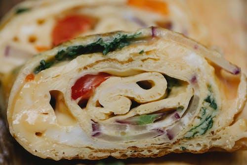 Appetizing vegetable egg roll slice on wooden board