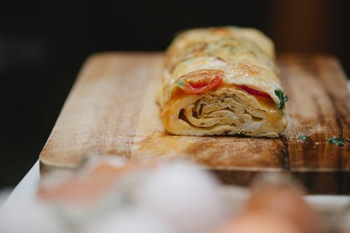 Appetizing yummy egg roll with ripe vegetables and fresh herbs placed on cutting board