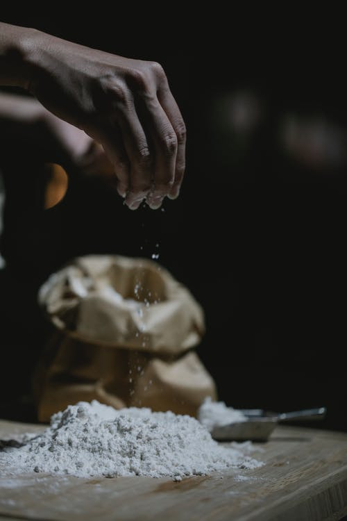 Crop anonymous cook sprinkling flour while standing at table and preparing dough in kitchen