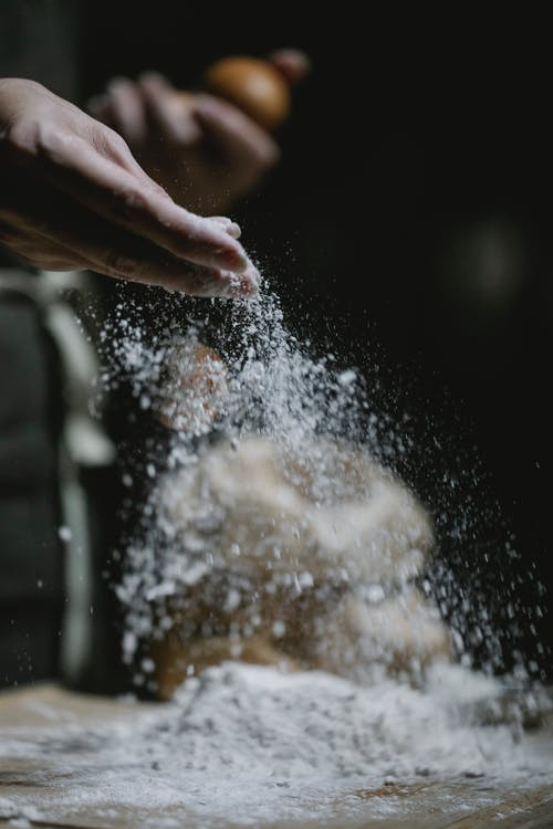 Crop baker scattering powdered flour on table