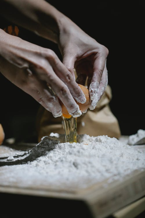 Crop anonymous baker breaking egg to flour while standing at table and cooking dough