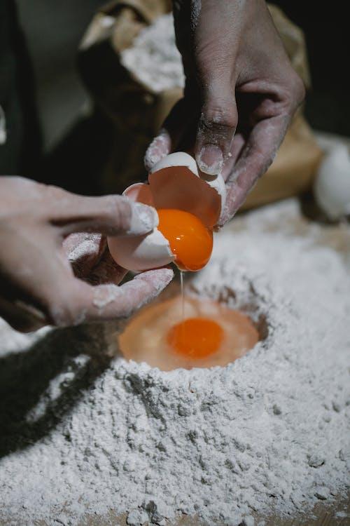 Chef adding egg to flour for dough recipe