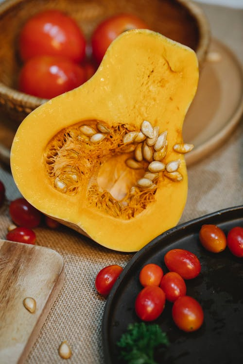 From above of ripe pumpkin with seeds placed near bowl of tomatoes on table for cooking