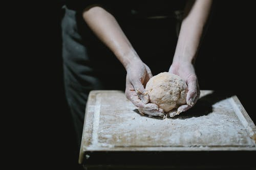 From above of crop anonymous cook kneading dough on wooden board with flour