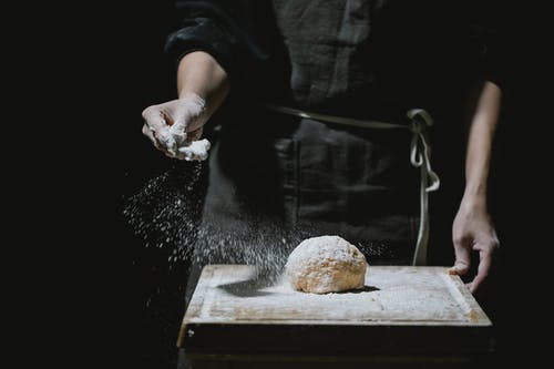 Unrecognizable baker in uniform standing at table and sprinkling flour in dough while cooking against black background