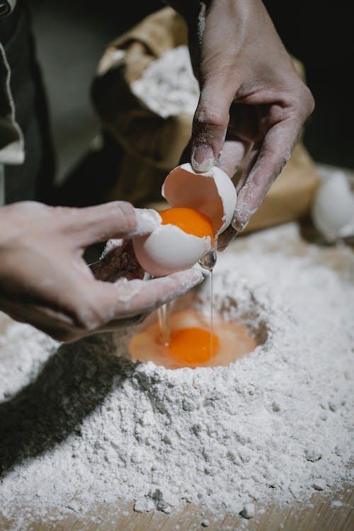Cook breaking egg on flour for recipe