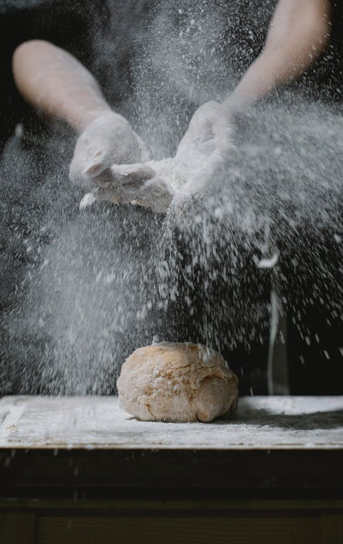 Crop anonymous chef standing at table and scattering flour on dough during cooking process