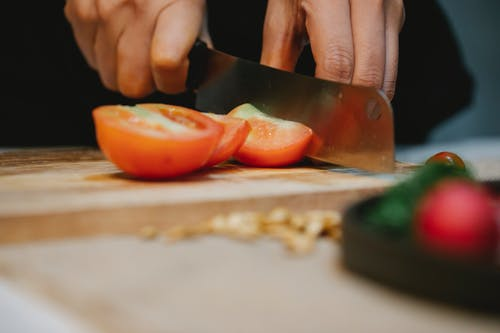 Chef slicing tomato on chopping board in kitchen