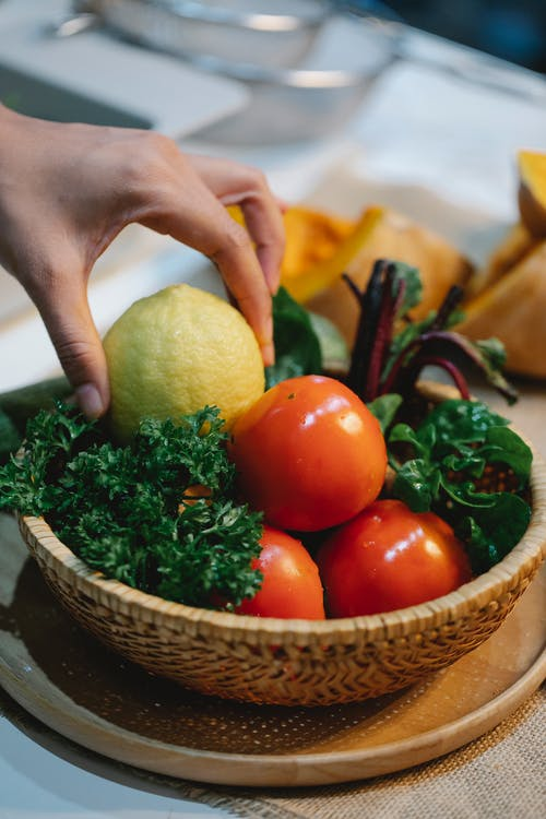 High angle of crop anonymous female taking ripe lemon from wicker bowl with wet tomatoes and parsley