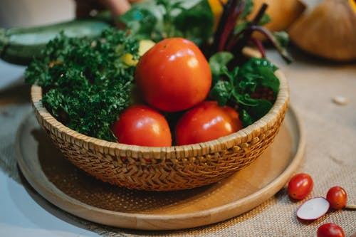 High angle of whole fresh tomatoes with herbs in wicker bowl placed on table in kitchen