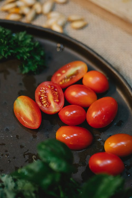 Fresh cherry tomatoes with herbs on table
