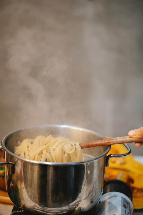 Woman cooking spaghetti in steaming water