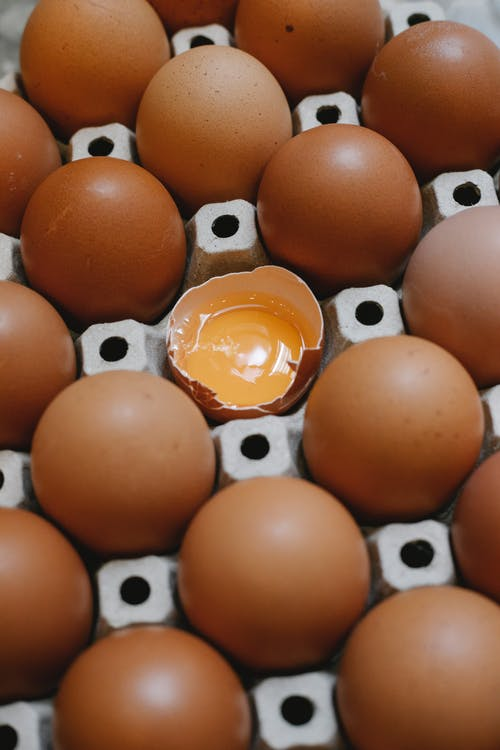 From above of carton container with chicken eggs placed near broken and prepared for cooking