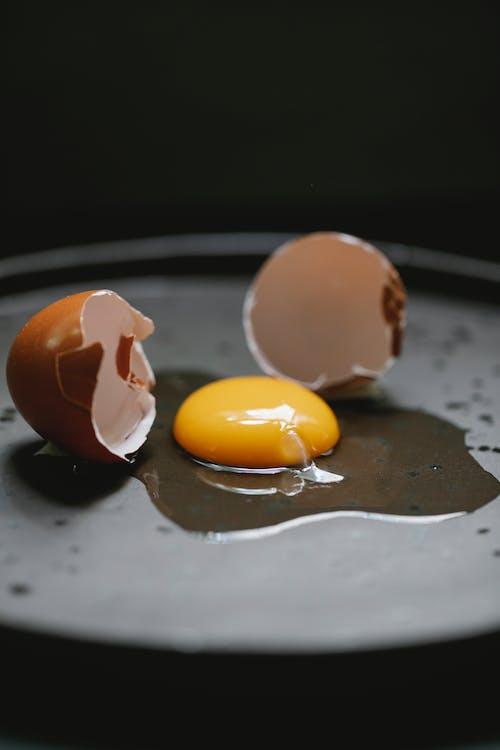 Broken chicken egg placed on black plate