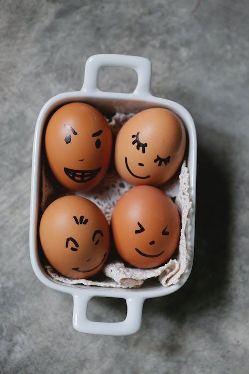 2 белых и коричневых яйца в лотке для белых яиц