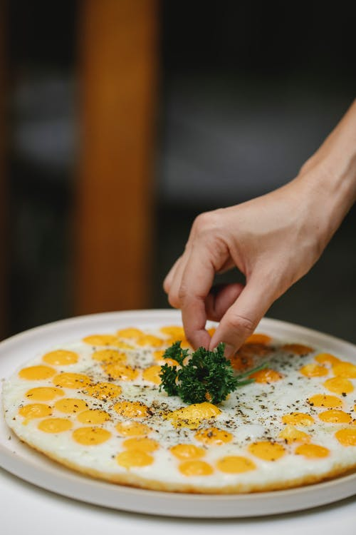 Crop anonymous chef putting green sprig of parsley on tasty fried eggs placed on plate against blurred background
