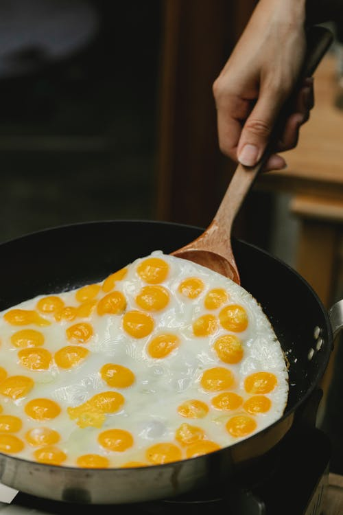 Crop anonymous chef preparing fresh delicious fried eggs in pan against blurred background