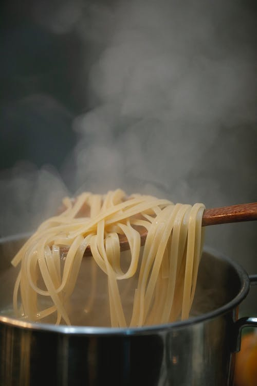 Fresh spaghetti boiling in metal saucepan in hot steam against dark background in room