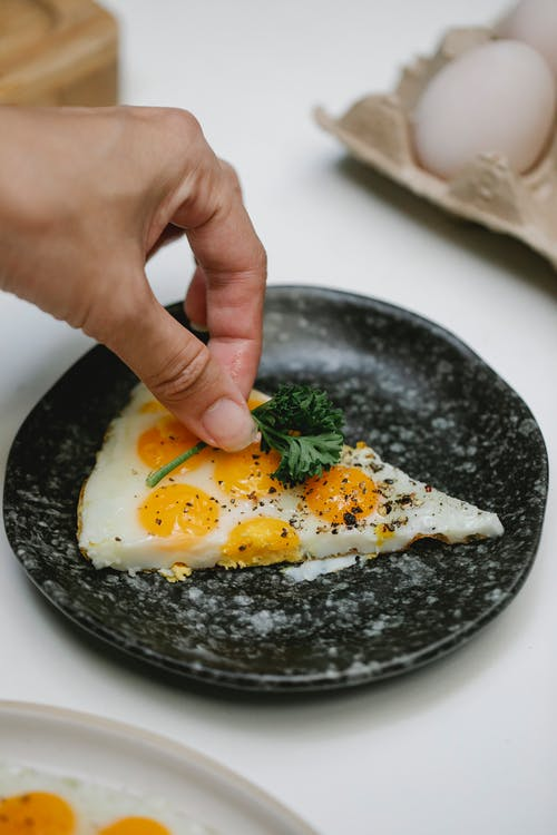 Chef adding sprig of parsley on fried eggs