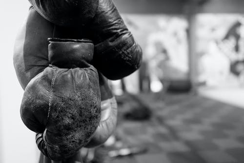 Grayscale Photo of Person Wearing Boxing Gloves