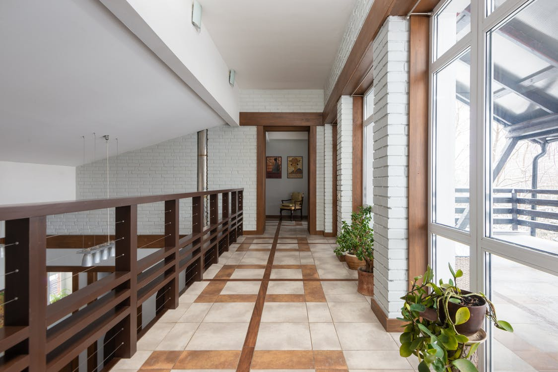 Long corridor with wooden railing and potted green flowers placed near bid windows located on second floor of contemporary house