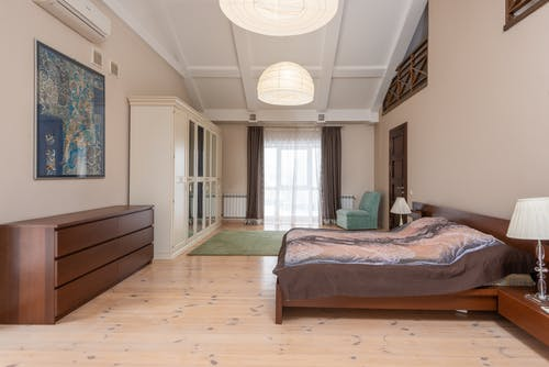 Spacious modern bedroom with bed placed against wooden cabinet near white wardrobe at wall with painting in light room with window