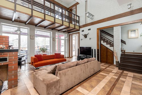 Interior of contemporary spacious apartment with comfortable sofas and big windows located in room with TV near staircase at home