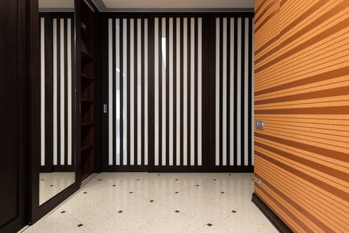 Interior of modern hallway with mirror and black striped decor and orange wall in apartment with tiled floor at home
