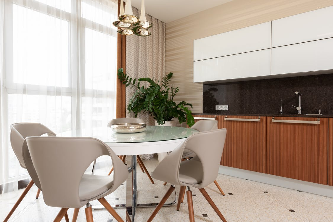 Plate on white round table with stools placed on tiled floor near green potted plant and counter with sink and wooden cupboards in dining room