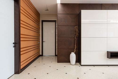 Interior of spacious hallway of modern apartment with door and white vase placed at wall on tiled floor at home