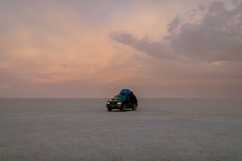 Lonely black automobile driving through empty sandy desert against cloudy sky in sunset