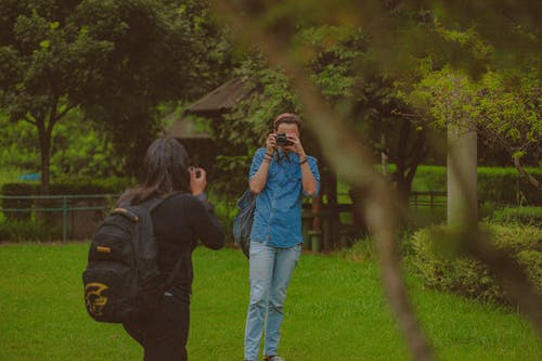 Anonymous man and woman with photo cameras taking pictures of each other while standing on grassy lawn in park with green trees