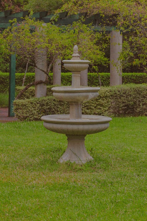 Aged stone fountain on grassy ground in park with pillars near green bushes and trees with lush foliage in nature
