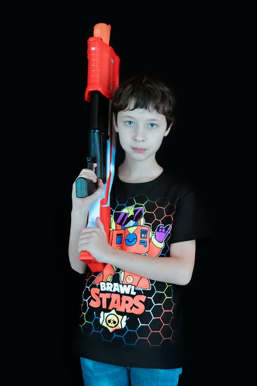 Cute kid with toy weapon in hand looking at camera in black studio