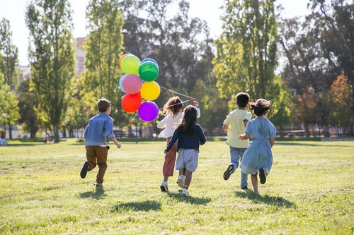 Children Playing With Balloons on Green Grass Field