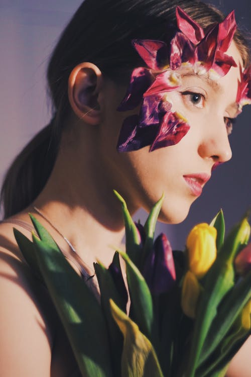 Crop emotionless woman with tulip flowers in studio