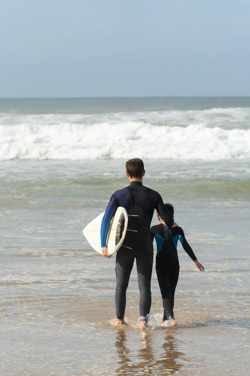 Man in Black Wet Suit Carrying White Surfboard Walking on Beach