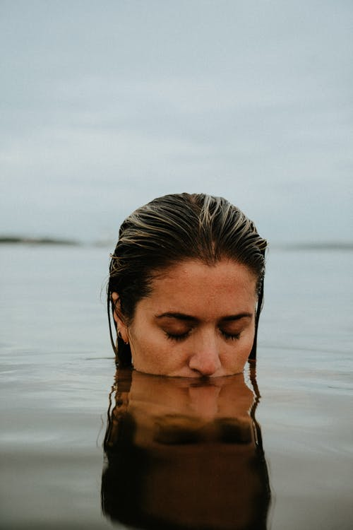 Thoughtful woman with wet hair standing in calm lake water