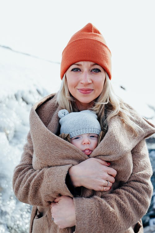 Happy mother hugging little girl under warm coat in winter