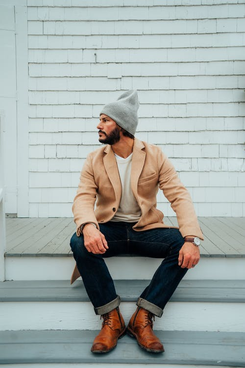 Stylish bearded man sitting on wooden staircase