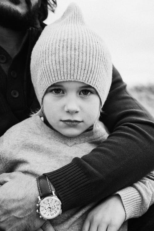 Black and white man standing behind and embracing content little daughter in warm sweater and hat while standing in nature