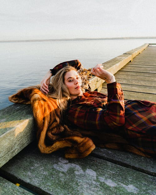 Young serene female in checkered dress lying on fur coat on wooden pier near peaceful sea while looking at camera and smelling wild flowers
