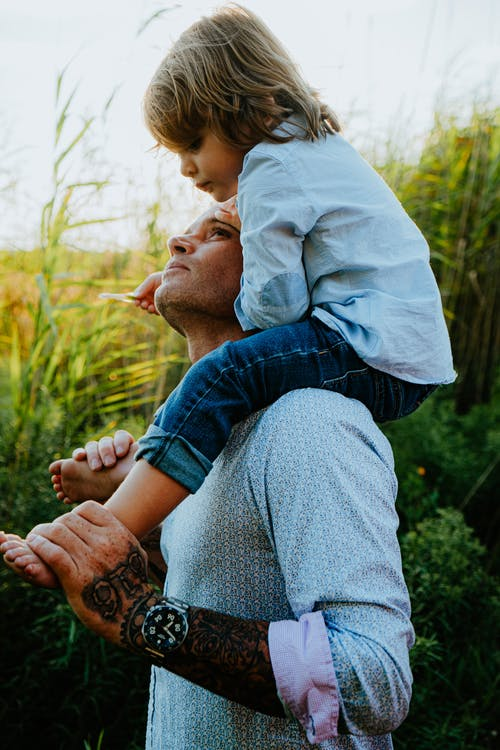 Father carrying little son on shoulders in grassy field