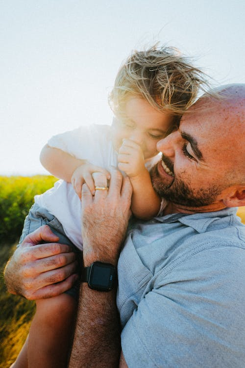 Cheerful father carrying little son in lush nature