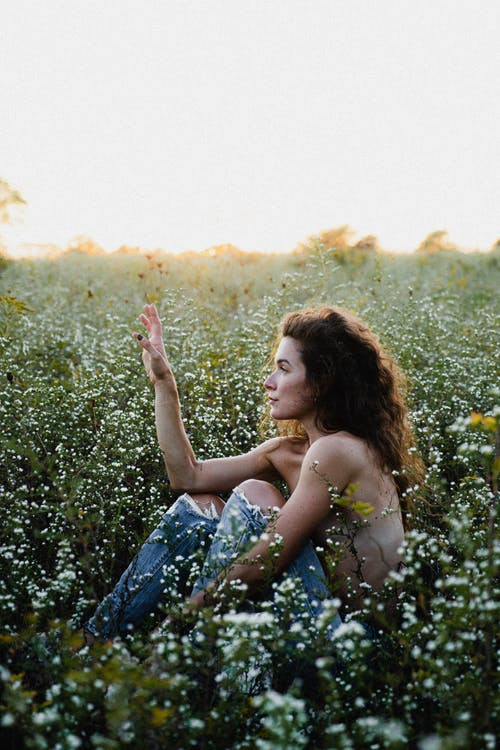 Tender topless woman sitting on grassy meadow