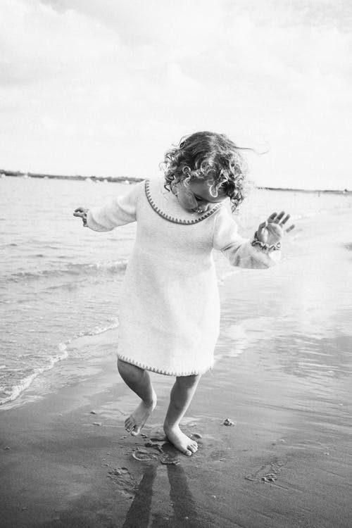 Black and white adorable little barefoot girl with curly hair in stylish white dress dancing on wet sandy seashore
